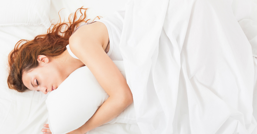Red-haired woman sleeping on a white sheets