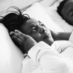 woman sleeping in the bed with a snoring man