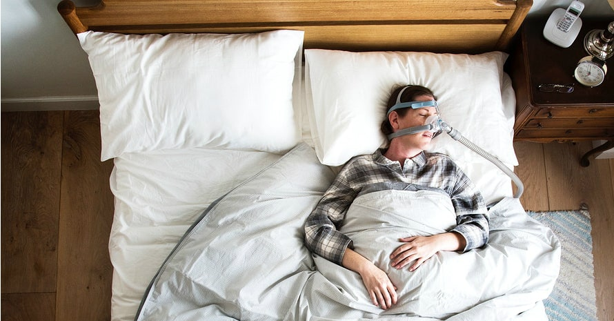 woman sleeping in the bed with a special snoring mask - cpap