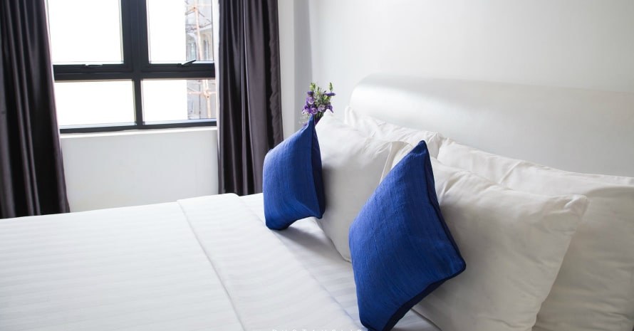 nice bed with white sheets and blue pillows