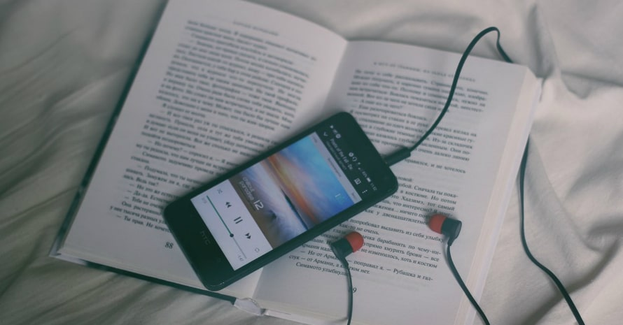 smartphone with earbuds and the book lying on the bed