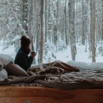 bed in front of the window with winter forest